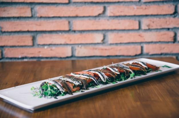 Retrato de placa con anchoas de tomate y pescado. concepto de cocina