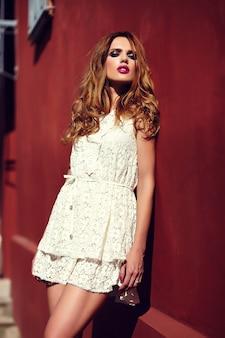 Retrato de portarretrato de glamour de alta moda de la hermosa y elegante modelo de mujer joven rubia elegante con maquillaje brillante y labios rosados con piel limpia perfecta en vestido blanco de verano cerca de la muralla roja