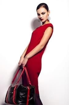 Retrato de portarretrato de glamour de alta moda de hermosa morena sexy elegante modelo de mujer joven caucásica en vestido rojo con bolsa negra de maquillaje brillante, con labios rojos, con piel limpia perfecta en estudio