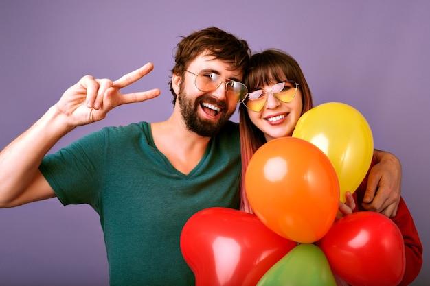 Retrato positivo brillante de la feliz pareja bonita sonriendo, mostrando gesto de paz y sosteniendo globos de fiesta, relación familiar, pared violeta