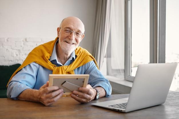 Retrato de positivo exitoso empleado senior atractivo con barba gris trabajando en el interior de la oficina moderna, usando la computadora portátil, sosteniendo el marco de fotos y sonriendo mientras extraña a sus nietos