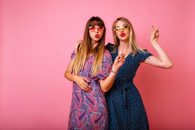 Retrato positivo de las mejores amigas hipster hermanas abrazos sonriendo y haciendo besos al aire, relaciones de amistad, juntos para siempre, pared rosa, trajes de verano de moda.