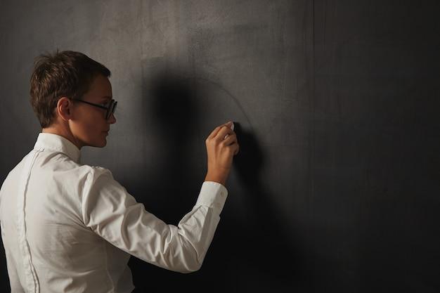Retrato posterior de una profesora seria en una camisa blanca comenzando a escribir en una pizarra vacía