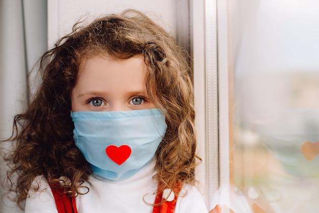 Retrato preescolar niño sentado en el alféizar de la ventana en casa, con máscara de virus con corazón rojo, niña mira a la cámara. epidemia pandémica propagando coronavirus 2019-ncov. concepto de día de enfermera.
