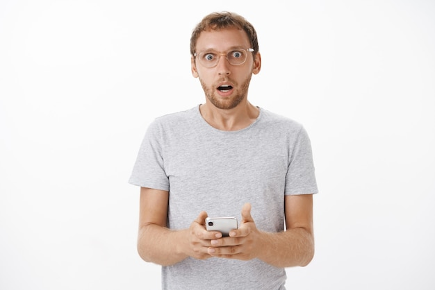 Retrato de preocupado conmocionado macho barbudo maduro jadeando abriendo la boca conmocionado sosteniendo el teléfono inteligente mirando la lectura de mensajes extraños e inquietantes posando