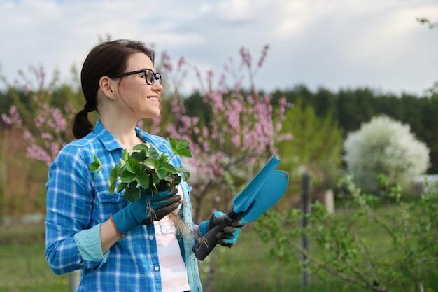 Retrato de primavera de mujer en jardín con herramientas, arbustos de fresa.