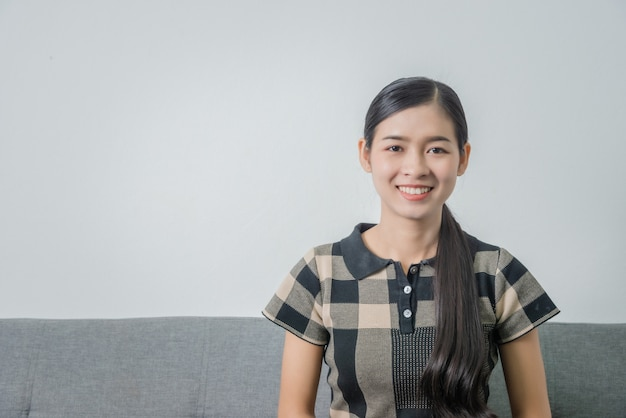 Retrato del primer de una muchacha asiática linda del estudiante mientras que se sienta en el sofá.