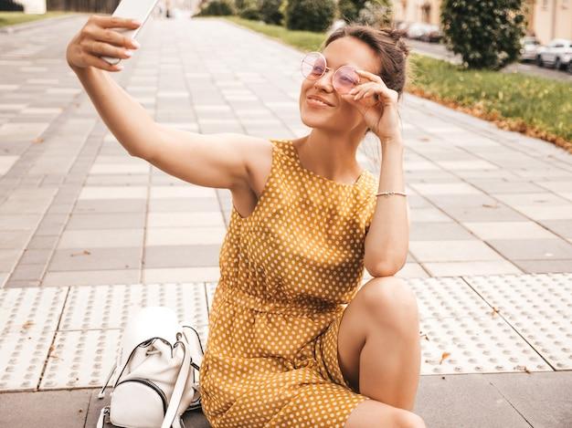 Retrato del primer de la muchacha morena sonriente hermosa en vestido amarillo del inconformista del verano. modelo tomando selfie en teléfono inteligente. mujer haciendo fotos en un día cálido y soleado en la calle con gafas de sol