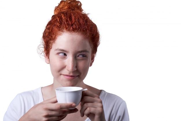 Retrato del primer de la muchacha pelirroja con las pecas que bebe de una taza
