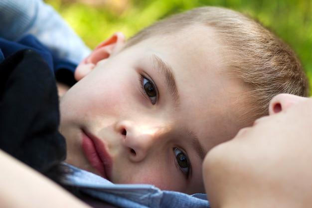 Retrato del primer del muchacho lindo del niño hermoso con los ojos soñadores grises al aire libre que ponen en hierba verde cerca de madre en día de verano soleado cálido. felices relaciones familiares entre madre e hijo, amor y confianza.