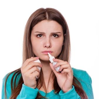 Retrato del primer de una mujer adolescente con alergia o frío, aislado en el fondo blanco con el espacio de la copia