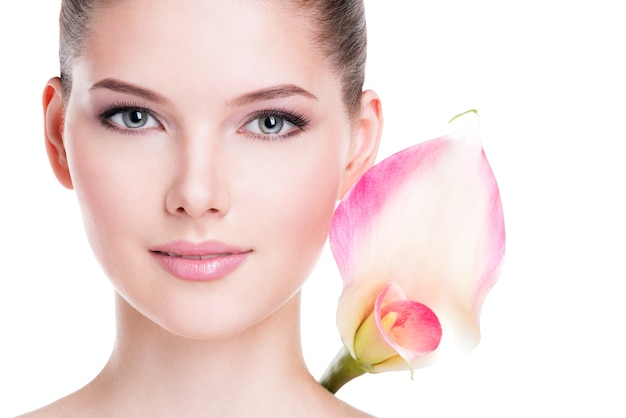 El retrato del primer de la mujer bonita joven hermosa con la piel sana y las flores rosadas cerca de la cara - aislada en blanco.