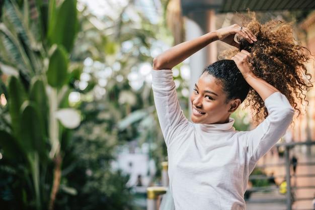 Retrato del primer de una mujer joven hermosa que ata su pelo rizado.