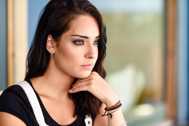 Retrato del primer de la mujer joven con los ojos azules al aire libre.