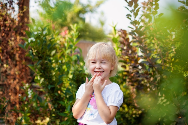 Retrato del primer de la pequeña muchacha feliz de blobde en edad de escuela primaria al aire libre en parque verde