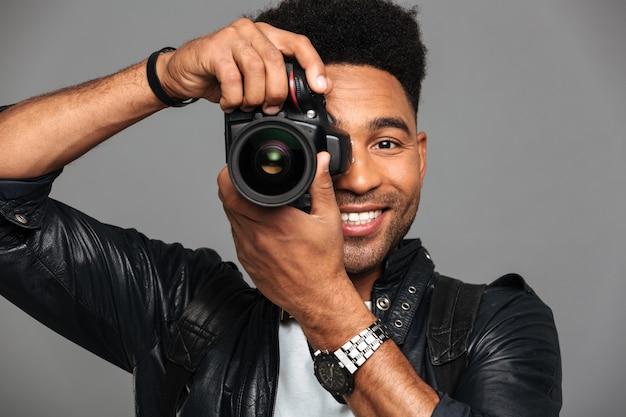 Retrato de primer plano del alegre hombre africano mirando a través de cámaras objetivo mientras toma la foto