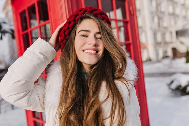 Retrato de primer plano de la alegre mujer de pelo largo con sombrero rojo posando delante de la cabina telefónica. foto al aire libre de la encantadora dama europea en boina tejida de pie junto a la cabina.