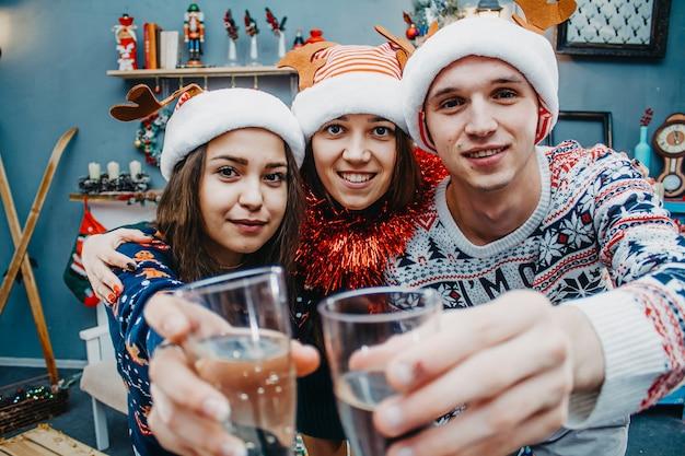 Retrato de primer plano de amigos con champán y sombreros de santa