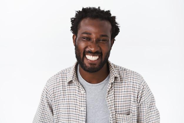 Retrato de primer plano, apuesto joven barbudo afroamericano alegre en camisa a cuadros, camiseta gris