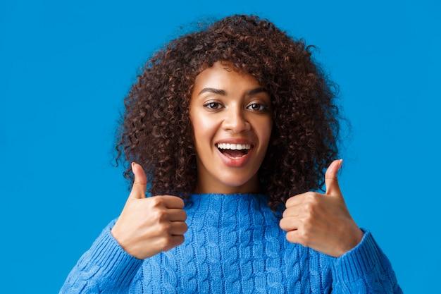 Retrato de primer plano de asertiva mujer afroamericana de pelo rizado satisfecho y satisfecho diciendo que está bien, acepte algo bueno, muestre aprobación con el pulgar, como regalo, de pie azul