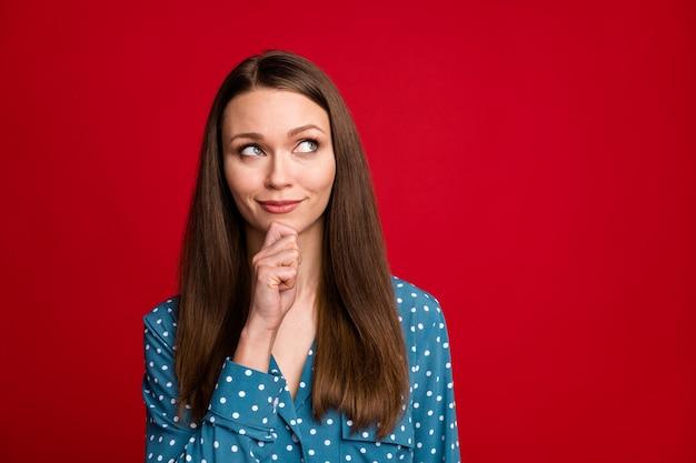 Retrato de primer plano de la atractiva chica de pelo castaño alegre inteligente pensando tocar la barbilla copia espacio aislado de fondo de color rojo brillante