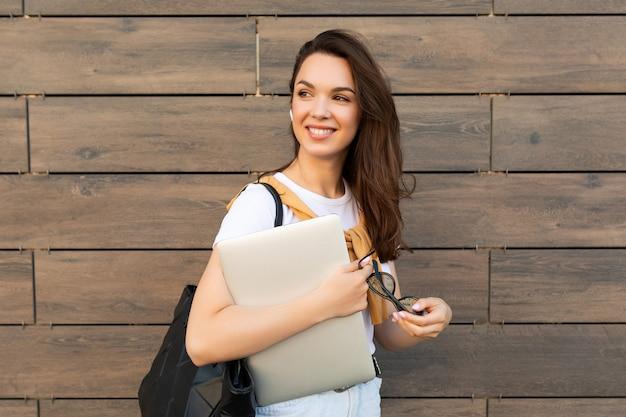 Retrato de primer plano de atractiva encantadora atractiva encantadora fascinante alegre alegre dama morena de pelo recto mirando al lado en la calle con ordenador portátil y gafas en las manos.
