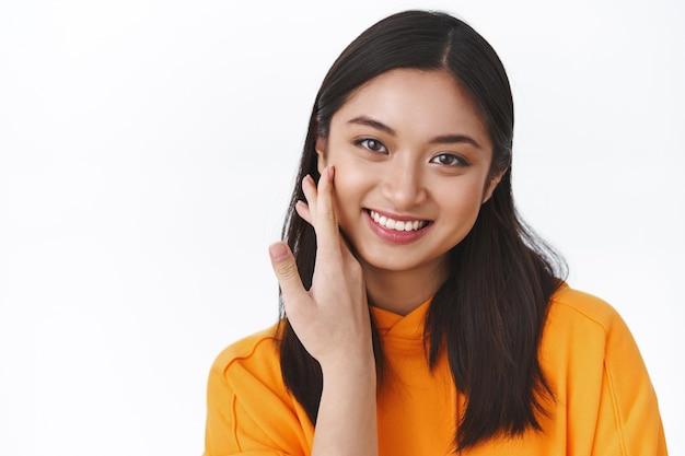 Retrato de primer plano atractiva joven asiática tocando la mejilla y sonriendo, no tener imperfecciones, aplicar productos para el cuidado de la piel, maquillaje coreano, pared blanca de pie