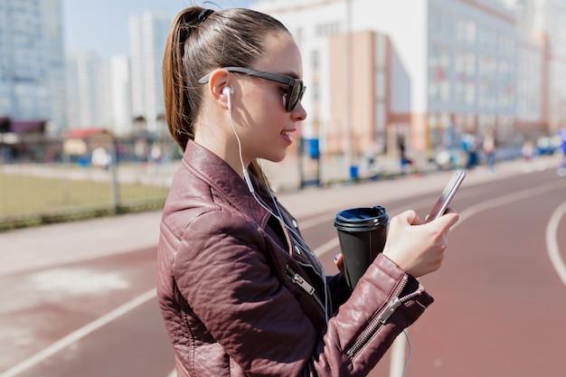 Retrato de primer plano de una bella dama con cabello oscuro recogido usa gafas de sol negras, bebe café, mira en el teléfono y escucha música en auriculares