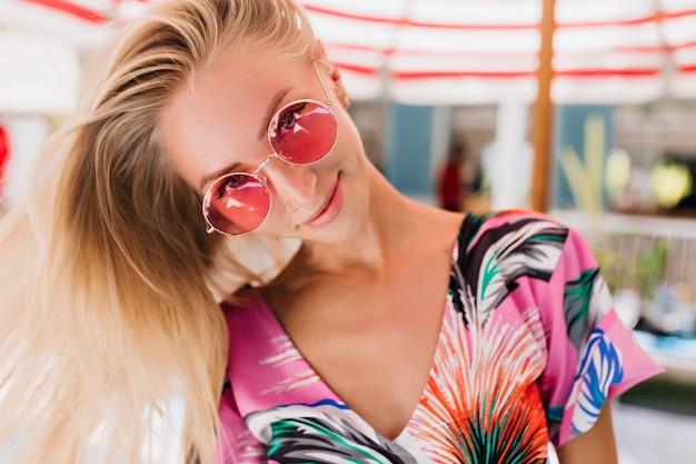 Retrato de primer plano de una chica increíble con gafas rosas divirtiéndose en el resort de verano.