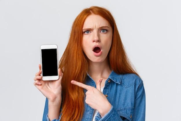 Retrato de primer plano chica pelirroja enojada y enojada mostrando fotos de ex novio de las redes sociales