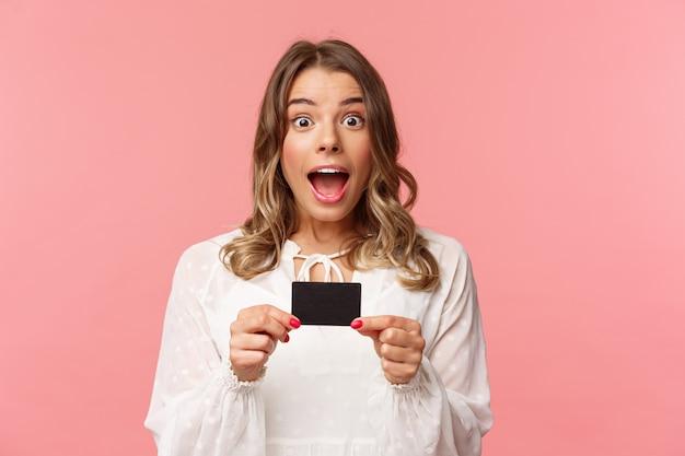 Retrato de primer plano de una chica rubia atractiva, emocionada, emocionada y emocionada que muestra la tarjeta de crédito y se siente muy feliz, informando sobre descuentos, ofertas especiales, servicio bancario, en una pared rosa
