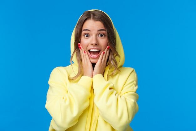 El retrato de primer plano de una chica rubia impresionada y fascinada con capucha reacciona a las increíbles noticias, toca las mejillas jadeando y sonriendo maravillado, escucha que ganó el premio, de pie