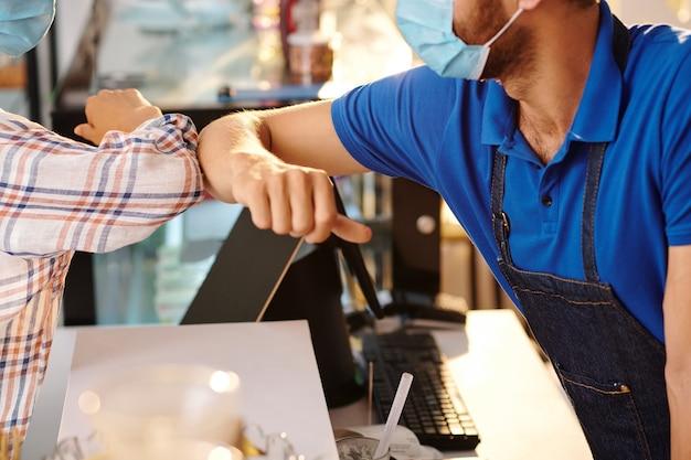 Retrato de primer plano de la clienta dando golpe de codo al barista de la cafetería