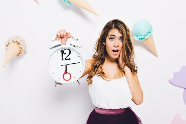 Retrato de primer plano de elegante joven vestida con estilo, posando con reloj blanco en la pared decorada. chica rizada de pelo largo con expresión de cara infeliz de pie delante de la pared con helado