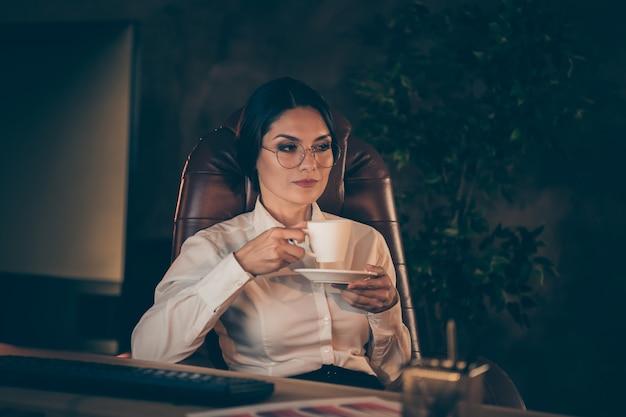 Retrato de primer plano de ella, agradable, atractiva, encantadora, elegante, experimentada, dama, experta en tiburones, especialista, propietario de la empresa, sentado en una silla, bebiendo espresso en la noche, estación de trabajo oscura en el interior