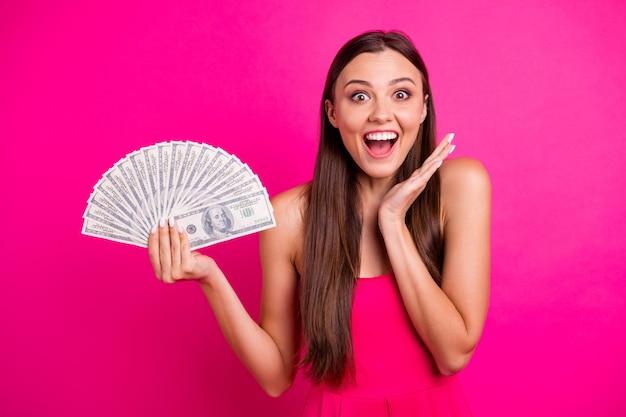 Retrato de primer plano de ella ella agradable atractivo alegre alegre contento impresionada chica de pelo largo sosteniendo en la mano gran presupuesto de suma aislado sobre fondo de color fucsia rosa vibrante brillante brillo vivo