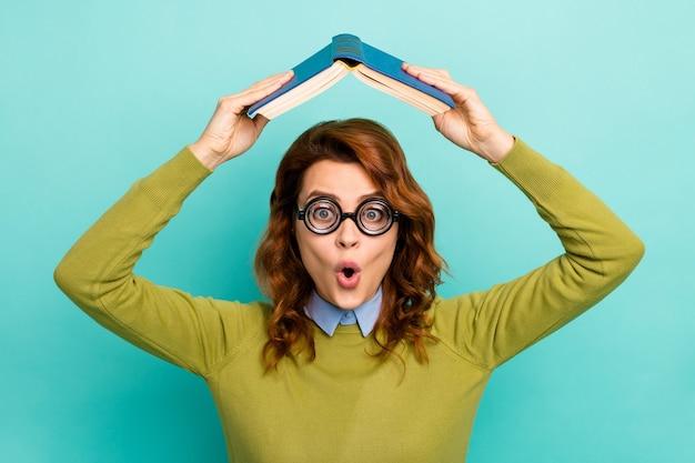Retrato de primer plano de ella ella agradable atractivo cómico funky divertido alegre chica de pelo ondulado sosteniendo libro como techo aislado sobre fondo de color turquesa verde azulado vibrante brillante brillo vivo