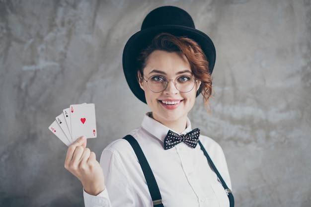 Retrato de primer plano de ella ella agradable contenido encantador encantador atractivo alegre alegre chica de pelo ondulado sosteniendo en las manos tarjetas de papel as tratar aislado sobre fondo de pared industrial de hormigón gris