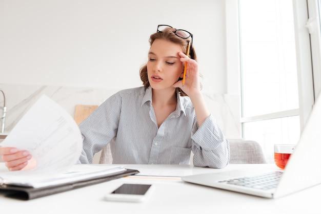 Retrato de primer plano de empresaria seria sosteniendo su cabeza mientras trabajaba con documentos en apartamentos ligeros