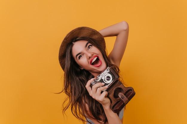 Retrato de primer plano de la encantadora fotógrafa riendo en el espacio colorido