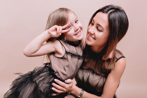 Retrato de primer plano de la encantadora linda chica y su elegante madre con vestidos negros similares en la pared beige