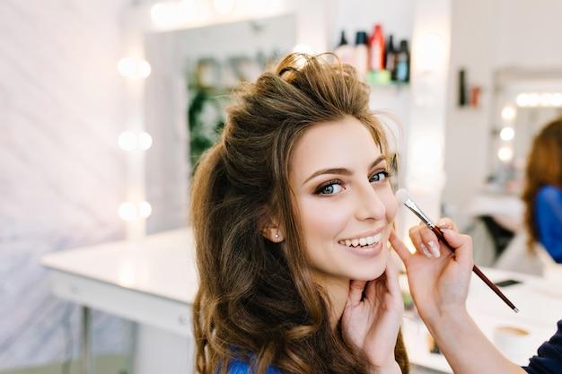 Retrato de primer plano con estilo de hermosa mujer joven con hermoso peinado sonriendo en salón de peluquería