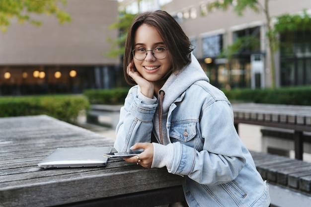Retrato de primer plano de una estudiante bastante joven alegre con el pelo corto, apoyarse en la palma de la mano mirando lindo a la cámara con una sonrisa feliz, sentado cerca de la computadora, usar la computadora portátil y el teléfono móvil al aire libre.
