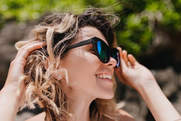 Retrato de primer plano de fascinante mujer emocional posando en la naturaleza. foto al aire libre de dama elegante con gafas brillantes de moda.