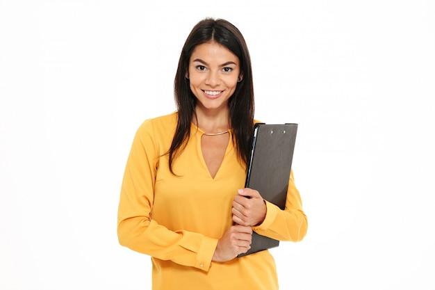 Retrato de primer plano de feliz exitosa mujer de negocios en camisa amarilla con carpeta con documentos