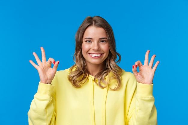 Retrato de primer plano feliz joven rubia confiada asegura que todo está bien, el plan de garantía fue bien, sonriendo y muestra un gesto de aprobación, confirmación o como, pie