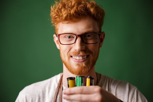 Retrato de primer plano del fotógrafo barbudo de cabeza lectora con gafas, sosteniendo rollos de cámara