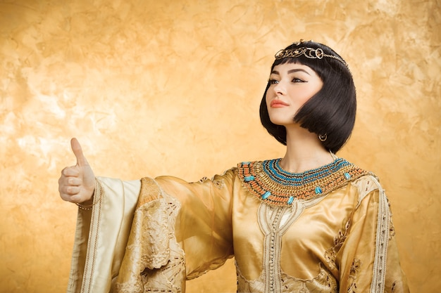 Retrato de primer plano glamoroso de la hermosa modelo sexy elegante mujer joven morena con maquillaje brillante con joyas de oro. cleopatra