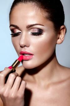 Retrato de primer plano de glamour de hermosa morena caucásica joven modelo aplicando maquillaje lápiz labial en sus labios con piel limpia perfecta