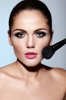 Retrato de primer plano de glamour de hermosa morena caucásica sexy modelo de mujer joven con piel limpia perfecta aplicar maquillaje en su rostro
